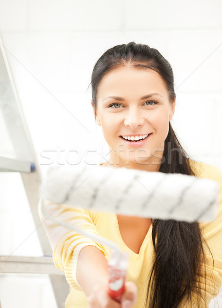 happy young woman with paintroller Stock photo © dolgachov