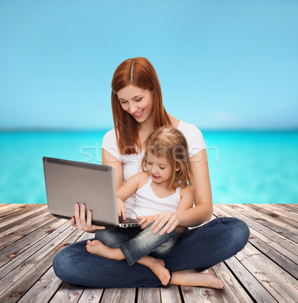 happy mother with adorable little girl and laptop Stock photo © dolgachov