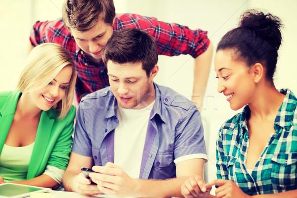 Foto d'archivio: Studenti · guardando · smartphone · scuola · istruzione · internet