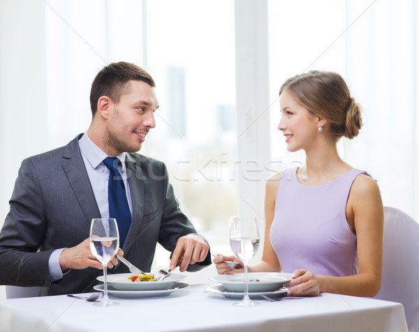 smiling couple eating appetizers at restaurant Stock photo © dolgachov