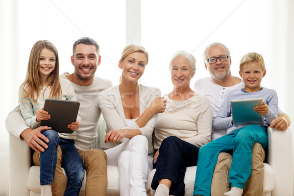 Stock photo: smiling family with tablet pc at home