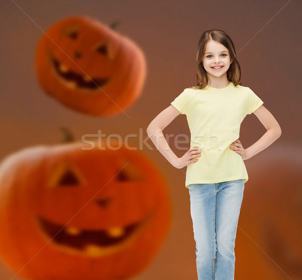 smiling girl over pumpkins background Stock photo © dolgachov