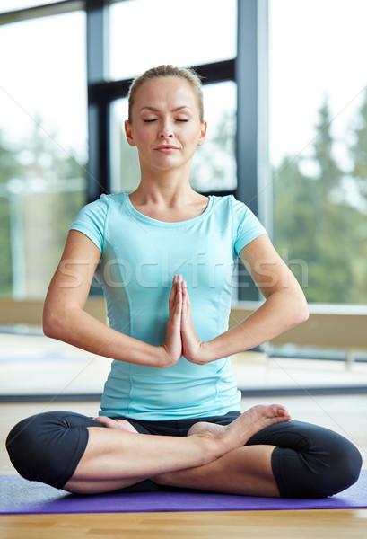 happy woman meditating in lotus pose on mat Stock photo © dolgachov