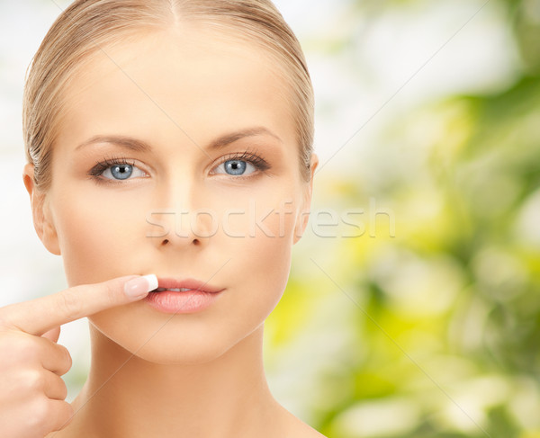 beautiful young woman pointing finger to her lips Stock photo © dolgachov