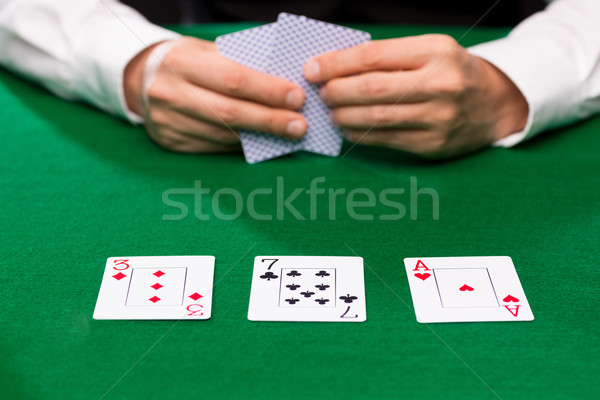 poker player holding playing cards at casino table Stock photo © dolgachov