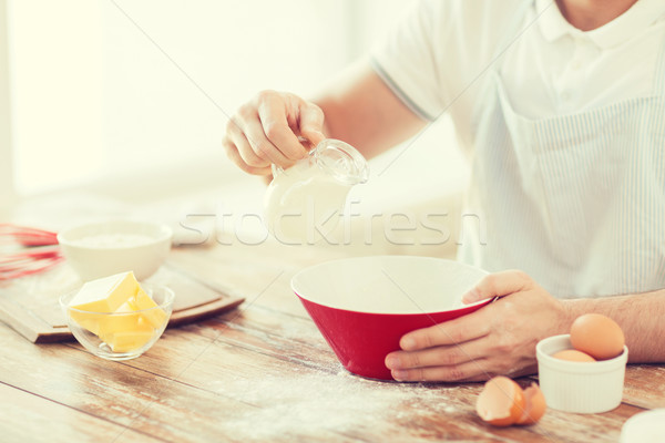 close up of male hand pouring milk in bowl Stock photo © dolgachov