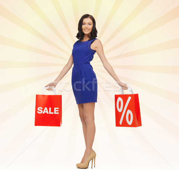 happy young woman in dress with red shopping bags Stock photo © dolgachov