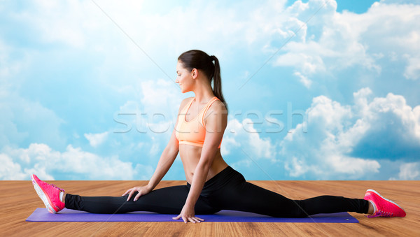 smiling woman doing splits on mat over clouds Stock photo © dolgachov