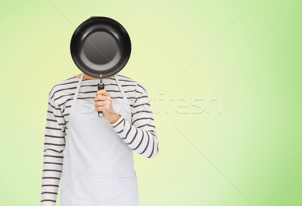 man or cook in apron hiding face behind frying pan Stock photo © dolgachov