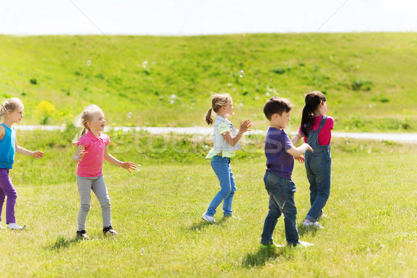 group of kids catching soap bubbles outdoors Stock photo © dolgachov