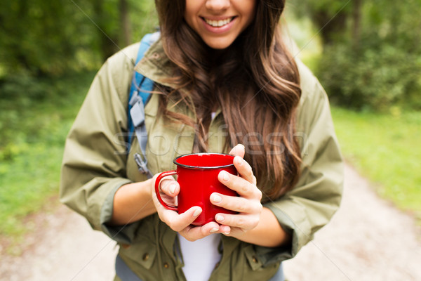 smiling young woman with cup and backpack hiking Stock photo © dolgachov