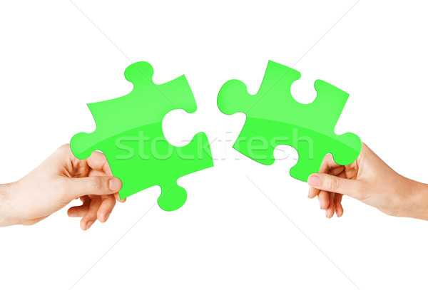 close up of couple hands with green puzzle pieces Stock photo © dolgachov
