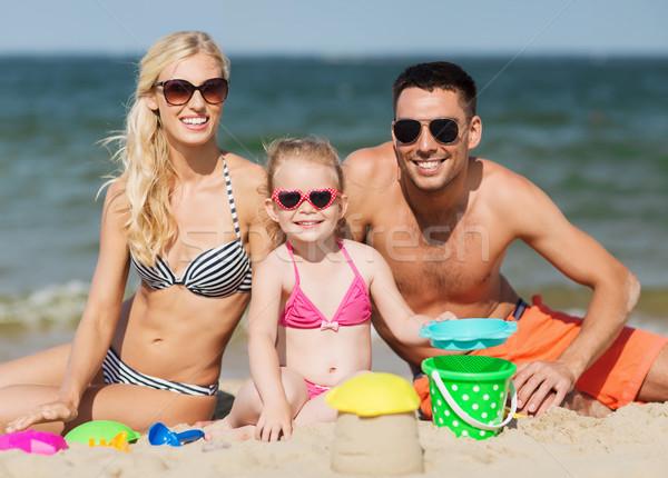 happy family playing with sand toys on beach Stock photo © dolgachov