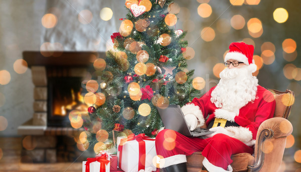 santa claus with laptop in armchair at home Stock photo © dolgachov