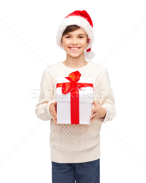 smiling happy boy in santa hat with gift box Stock photo © dolgachov
