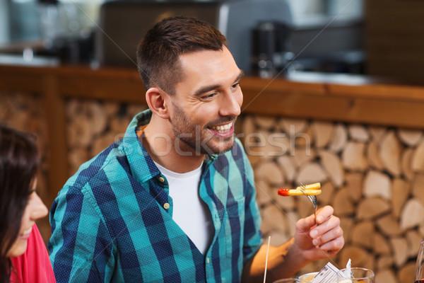 happy man having dinner at restaurant Stock photo © dolgachov