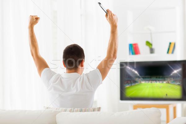 happy man watching football on tv at home Stock photo © dolgachov