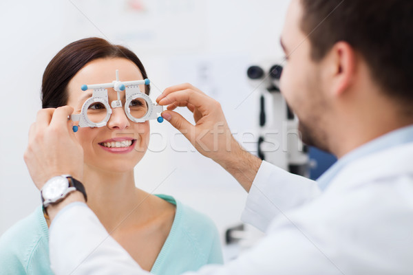 optician with trial frame and patient at clinic Stock photo © dolgachov