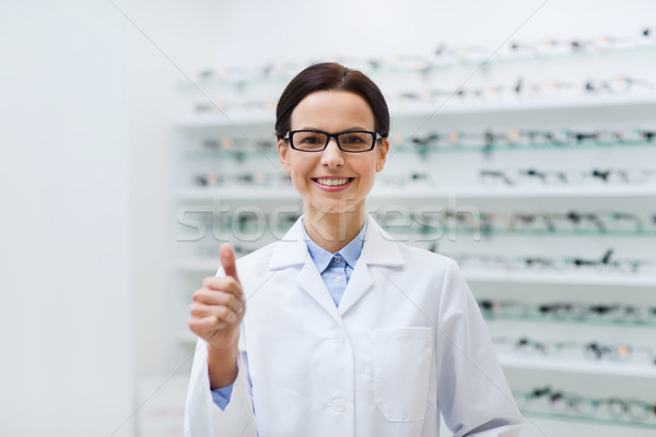 woman in glasses with thumbs up at optics store Stock photo © dolgachov