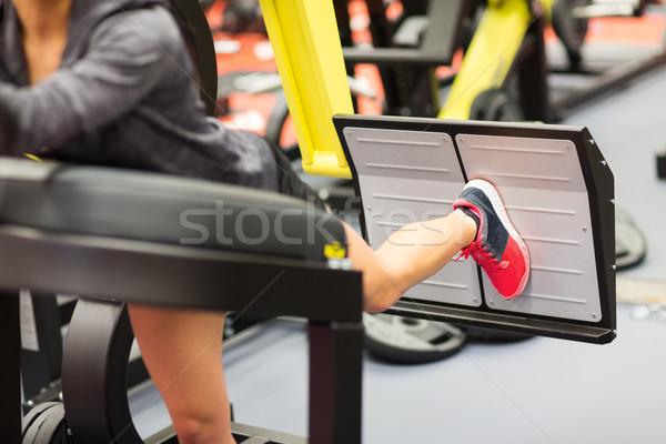Mulher músculos em imprensa máquina ginásio Foto stock © dolgachov