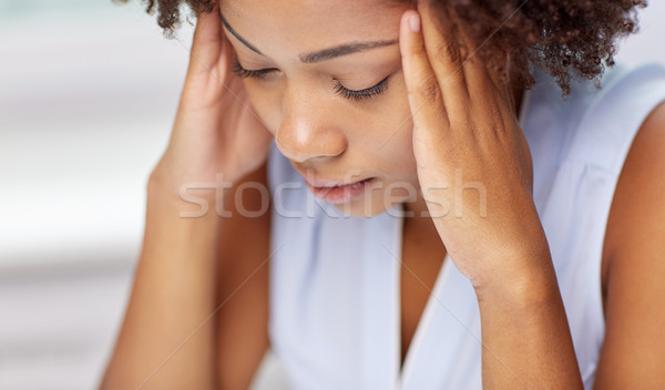close up of african young woman touching her head Stock photo © dolgachov