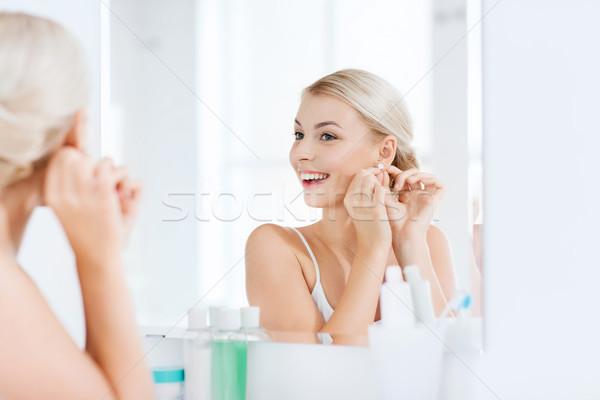 woman trying on earring looking at bathroom mirror Stock photo © dolgachov