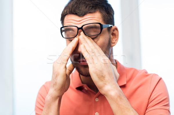 tired man in eyeglasses rubbing eyes at home Stock photo © dolgachov
