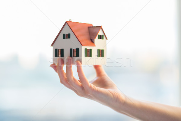 close up of hands holding house or home model Stock photo © dolgachov
