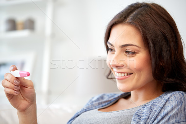 happy woman looking at home pregnancy test  Stock photo © dolgachov