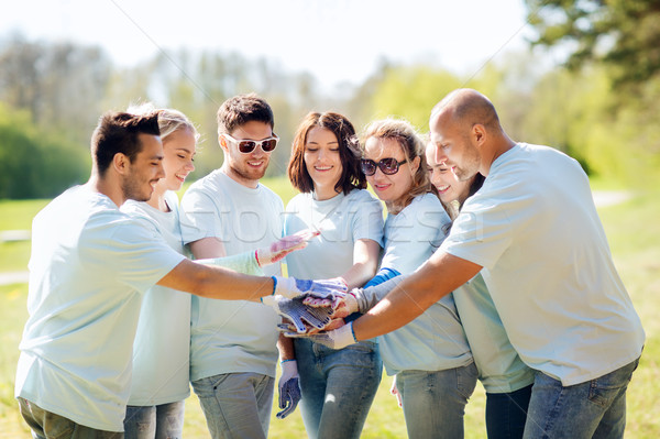 group of volunteers putting hands on top in park Stock photo © dolgachov