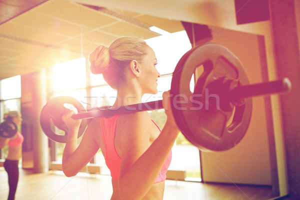 sporty woman exercising with barbell in gym Stock photo © dolgachov