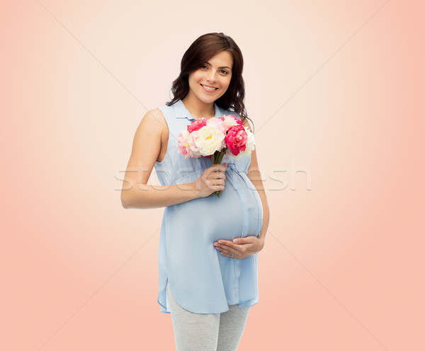 happy pregnant woman with flowers touching belly Stock photo © dolgachov