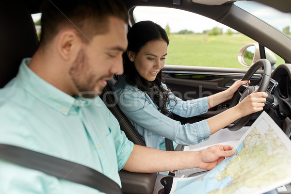 happy man and woman with road map driving in car Stock photo © dolgachov