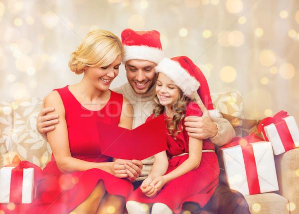 Uśmiechnięty rodziny czytania pocztówkę christmas Zdjęcia stock © dolgachov