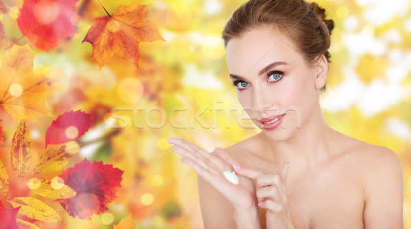 happy young woman with moisturizing cream on hand Stock photo © dolgachov