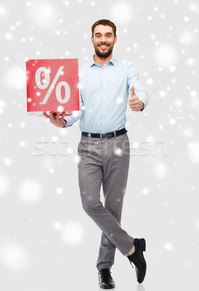 Sorridente homem vermelho percentagem assinar neve Foto stock © dolgachov