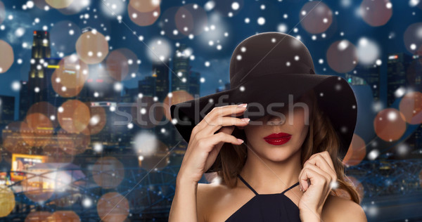 beautiful woman in black hat over night city Stock photo © dolgachov