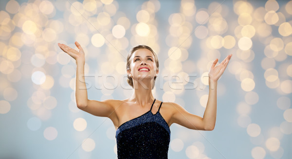 smiling woman raising hands and looking up Stock photo © dolgachov