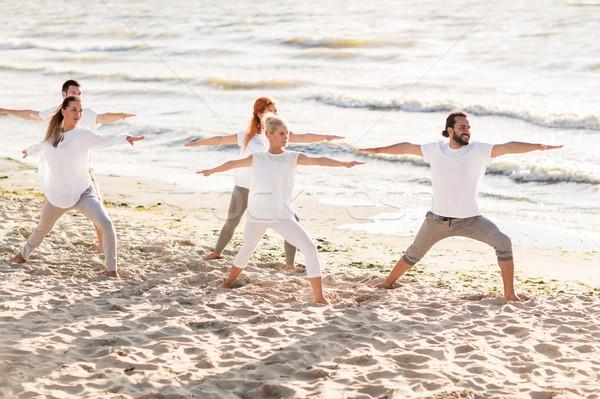 Personas yoga guerrero plantean playa Foto stock © dolgachov