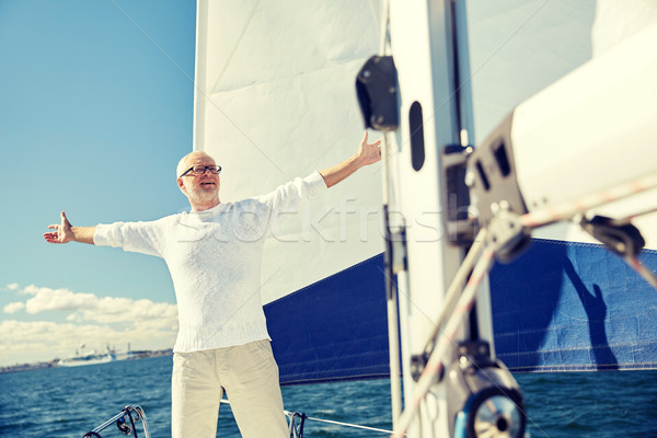 senior man on sail boat or yacht sailing in sea Stock photo © dolgachov