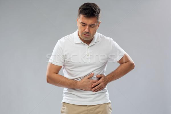 Boldogtalan férfi szenvedés gyomorfájás emberek egészségügy Stock fotó © dolgachov