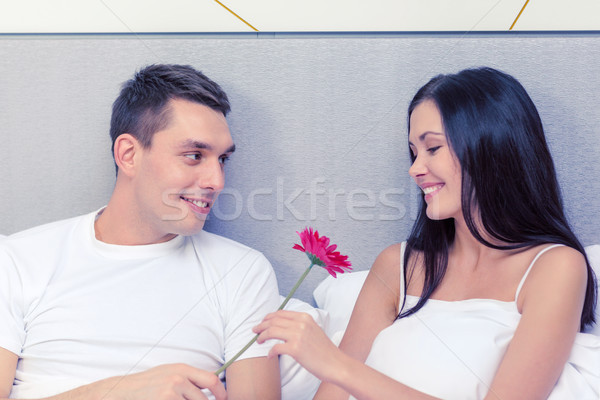 smiling couple in bed with flower Stock photo © dolgachov