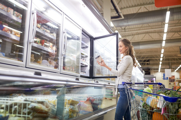 woman choosing ice cream at grocery store freezer Stock photo © dolgachov