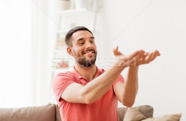 happy man holding something imaginary at home Stock photo © dolgachov