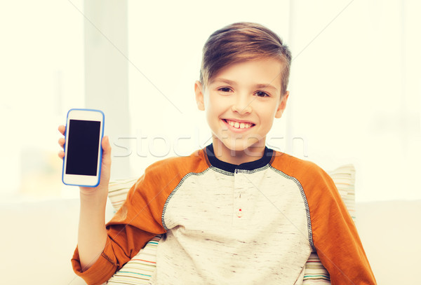 smiling boy with smartphone at home Stock photo © dolgachov