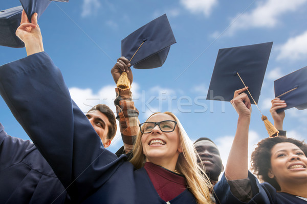 happy bachelors waving mortar boards over sky Stock photo © dolgachov