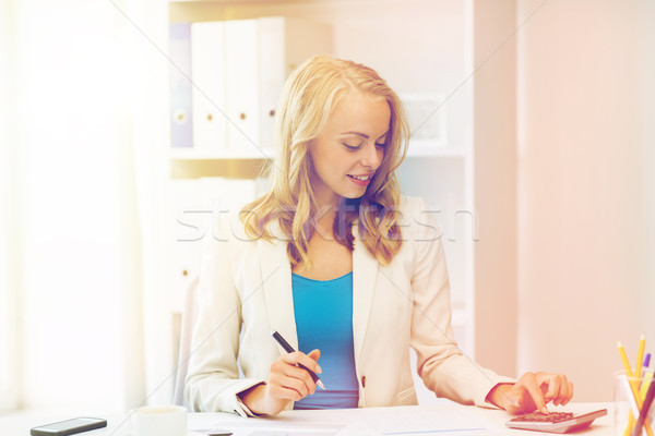businesswoman with calculator counting at office Stock photo © dolgachov