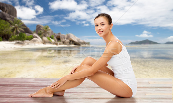beautiful woman touching her bare legs on beach Stock photo © dolgachov