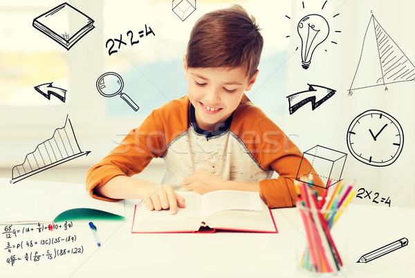 Mosolyog diák fiú olvas könyv otthon Stock fotó © dolgachov