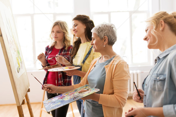 women with easel and palettes at art school Stock photo © dolgachov